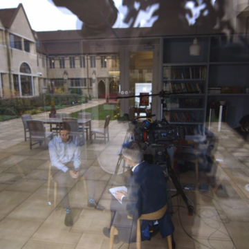 filming in the library with a reflection of the quad